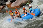 An Echo Canyon paddle crew charges into a wave in Sunshine Rapid of the famous Royal Gorge.