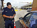 United States Customs and Border Protection:  A CBP officer processes a traveler as the cross the border from Mexico.