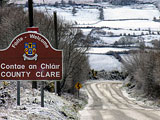 Welcome to Clare road sign set against fields dusted with snow.