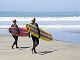 Half Moon Bay, California, surfer girls on the beach.