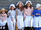 Visiting children don Shaker costumes in Discovery Room at Hacock Shaker Village.