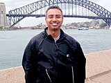 Author Tejas Desai in front of the Sydney Harbor Bridge, Australia.